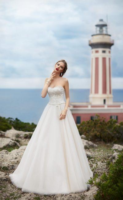 Классическое свадебное платье с многослойной юбкой и открытым корсетом с фигурным краем лифа.
