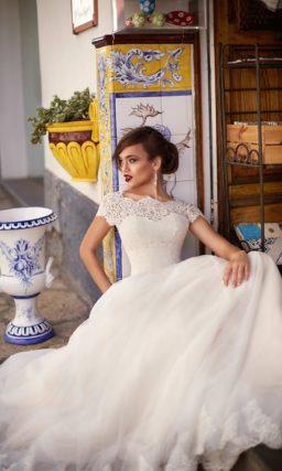Пышное свадебное платье с кружевным лифом и широким поясом на талии.