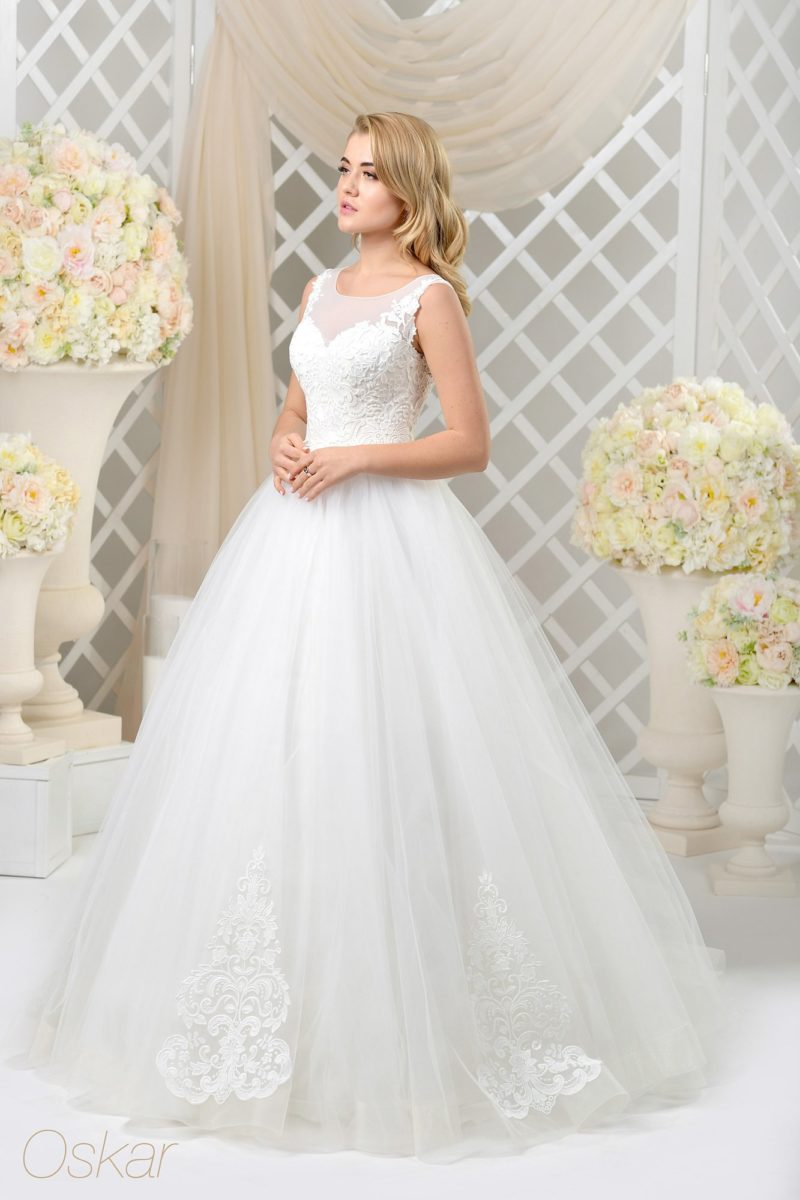 Закрытое свадебное платье с объемным низом и изящными аппликациями.