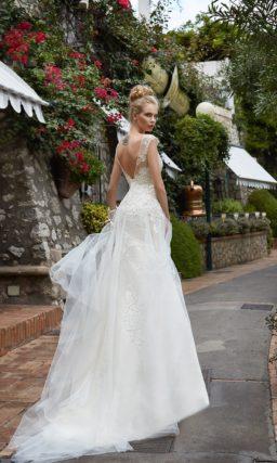 Фактурное свадебное платье с открытой спинкой и прямой юбкой с полупрозрачным верхом.