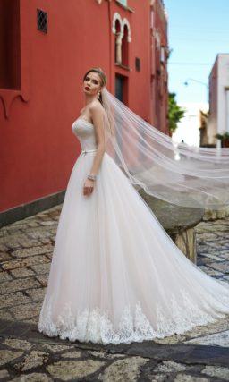 Прямое свадебное платье с кружевом по нижнему краю юбки и открытым корсетом.