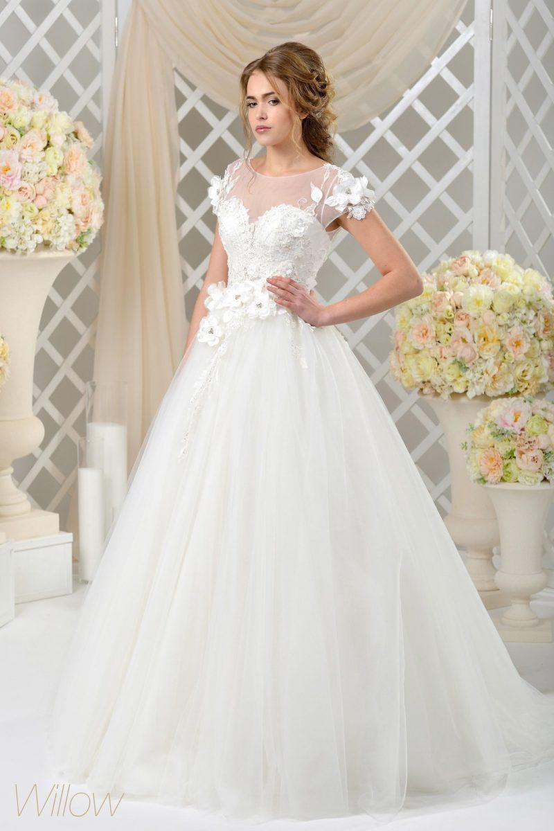 Кокетливое свадебное платье пышного кроя с романтичной объемной отделкой.