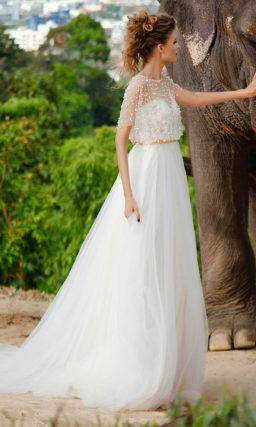 Пышное свадебное платье с закрытым верхом, украшенным бусинами, и кремовым поясом.