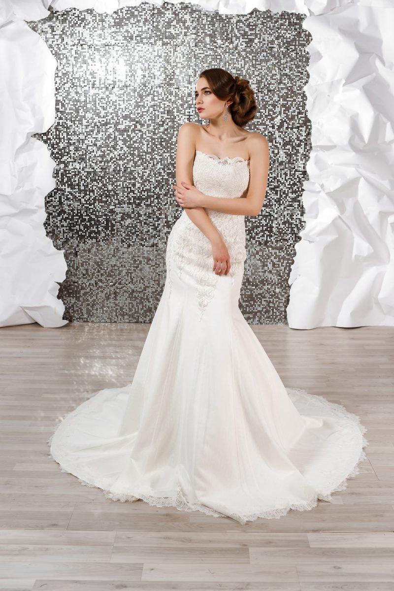 Открытое свадебное платье с прямым лифом и облегающим кроем, дополненным длинным шлейфом.