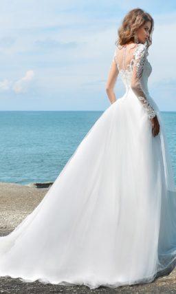 Свадебное платье с длинным рукавом, покрытым аппликациями, и пышной юбкой.