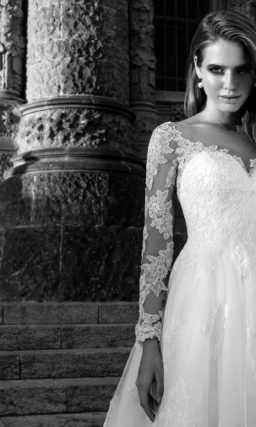 Пышное свадебное платье с длинным полупрозрачным рукавом и узким поясом с вышивкой.