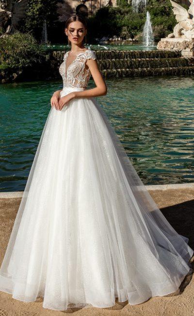 Романтичное свадебное платье с многослойным низом и тонким кружевным верхом.