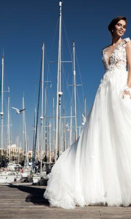 Очаровательное свадебное платье с обемной отделкой и пышной многослойной юбкой.