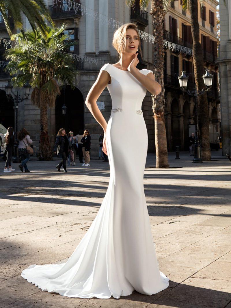 Утонченное атласное свадебное платье с закрытым верхом и длинным шлейфом сзади.