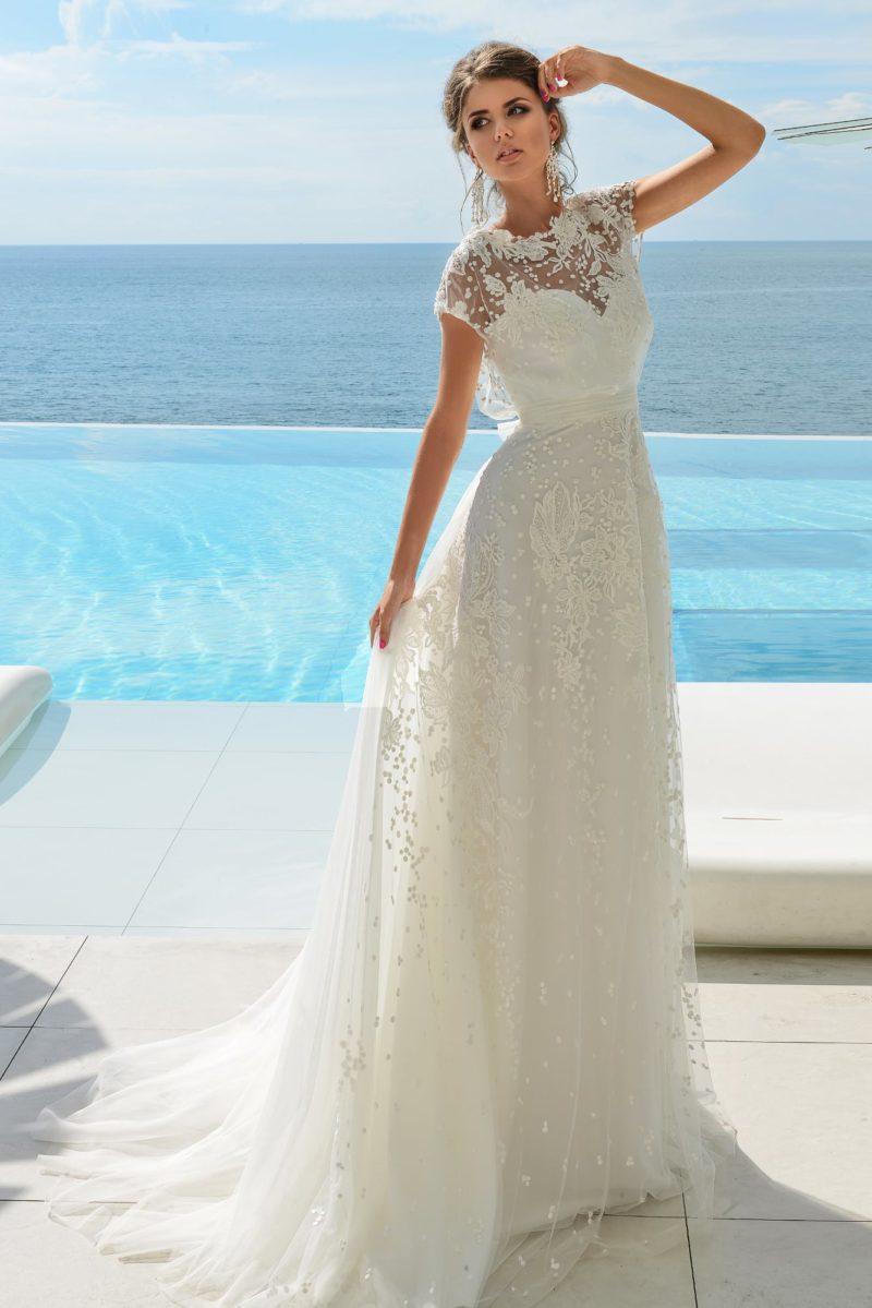 Прямое свадебное платье с закрытым верхом, декорированное оригинальным кружевом.