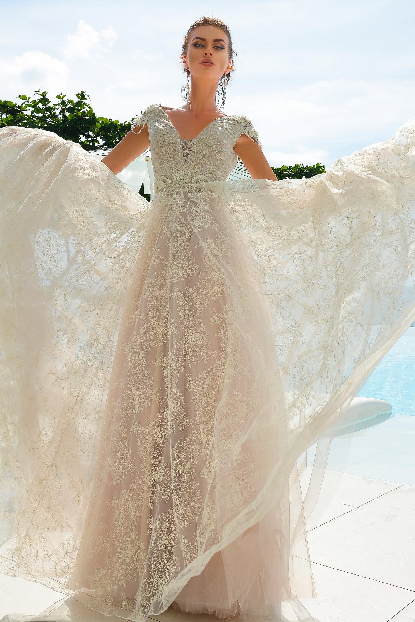Бежевое свадебное платье, оформленное по всей длине тонким цветочным кружевом.