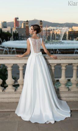 Атласное свадебное платье с вырезом под горло и эффектной пышной юбкой со шлейфом.
