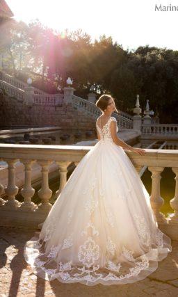 Пышное свадебное платье с ажурной отделкой верха и многослойным подолом бежевого цвета.