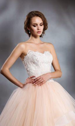 Свадебное платье с кружевным белым корсетом и многослойной юбкой персикового оттенка.