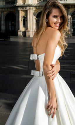 Открытое свадебное платье с пышной юбкой со скрытыми карманами, созданное из атласа.