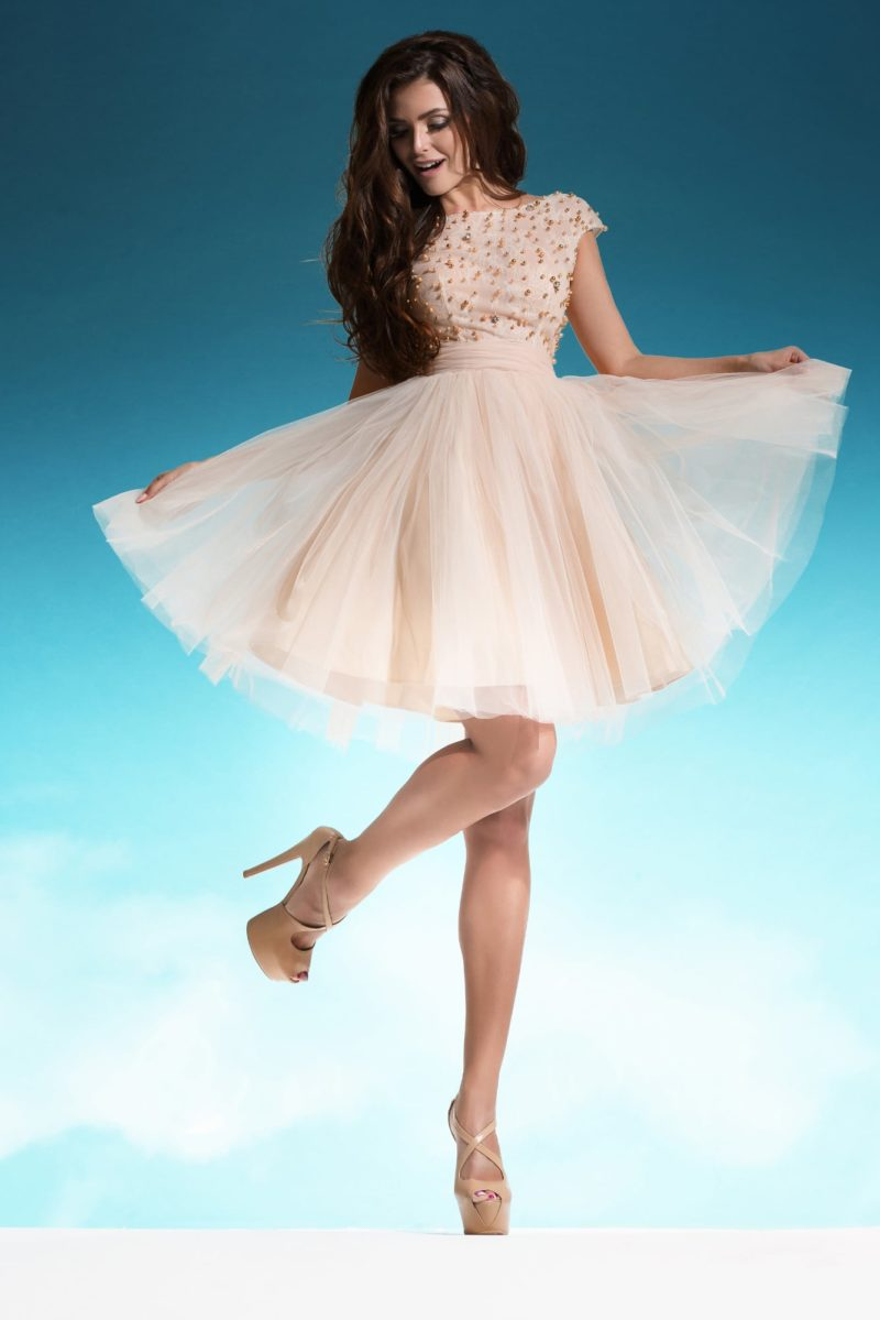Короткое свадебное платье пудрового оттенка с закрытым лифом, покрытым бусинами.