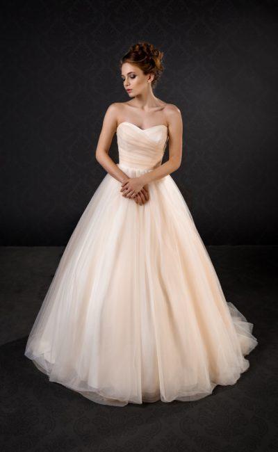 Лаконичное свадебное платье персикового оттенка с открытым лифом и пышной юбкой со шлейфом.