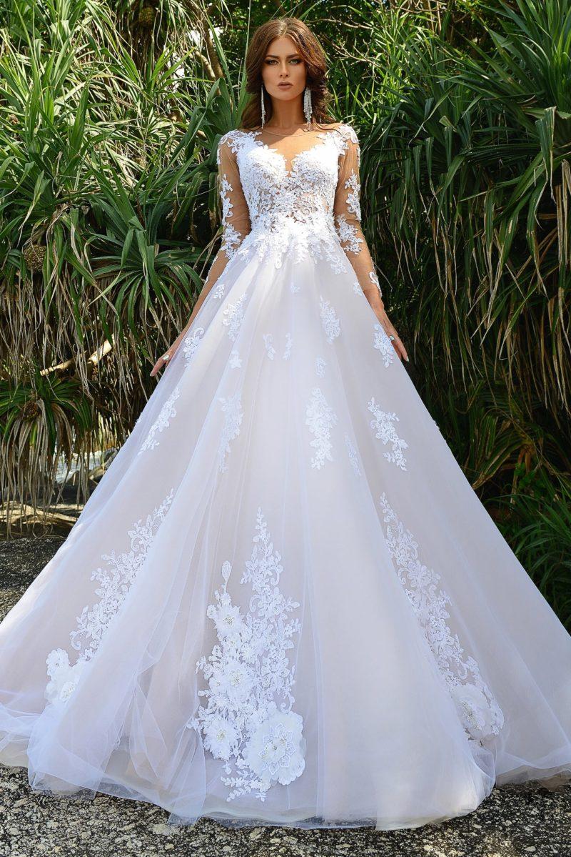 Пышное свадебное платье с длинным рукавом и закрытым лифом, украшенное кружевом.