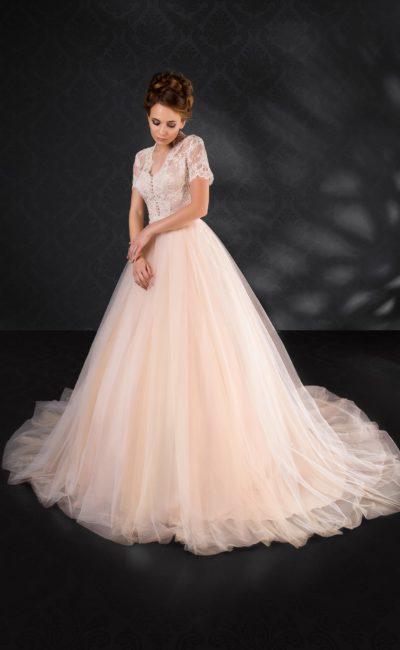 Персиковое свадебное платье с пышной юбкой и романтичным кружевным декором верха.