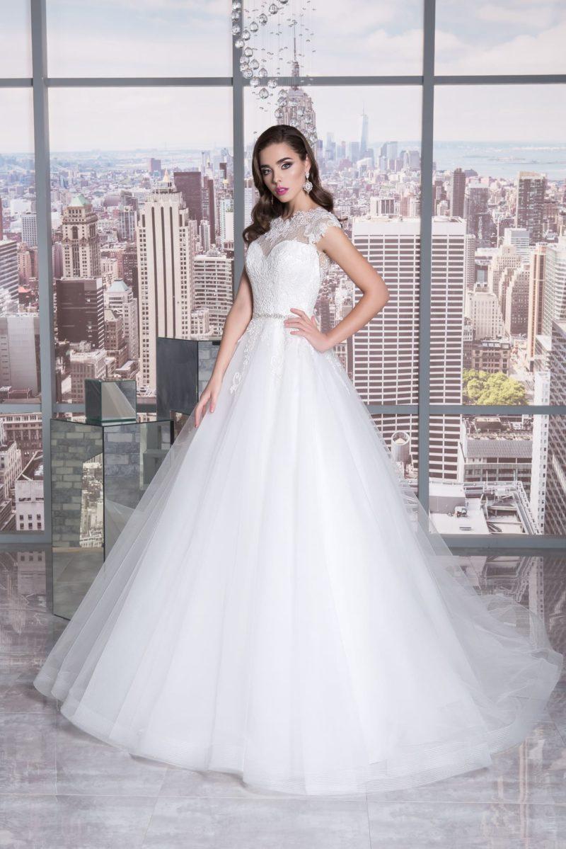 Пышное свадебное платье с очаровательным шлейфом и длинным рукавом из кружевной ткани.