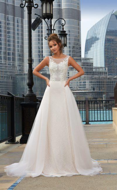 Закрытое свадебное платье с пышной верхней юбкой и фактурными аппликациями на корсете.