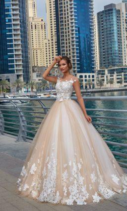 Пышное свадебное платье с многослойной бежевой юбкой и корсетом с белыми аппликациями.