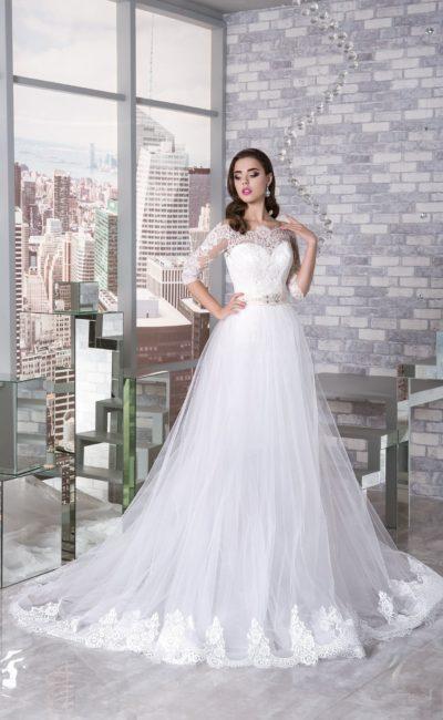 Пышное свадебное платье с многослойным подолом и кружевными рукавами до локтя.