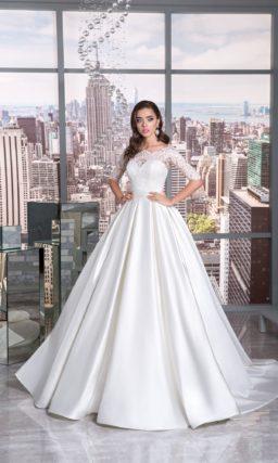 Пышное свадебное платье с атласной юбкой и элегантным кружевным верхом с рукавом до локтя.