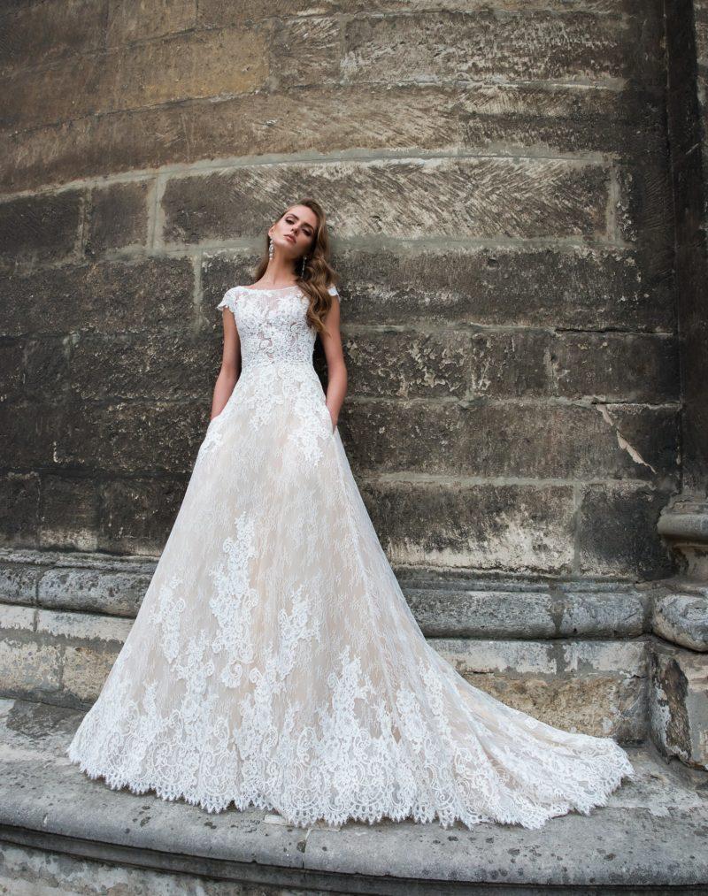 Свадебное платье «принцесса» с глубоким вырезом сзади и бежевой подкладкой на юбке.