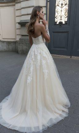 Кремовое свадебное платье с кружевным корсетом, подчеркивающим декольте лифом-сердечком.