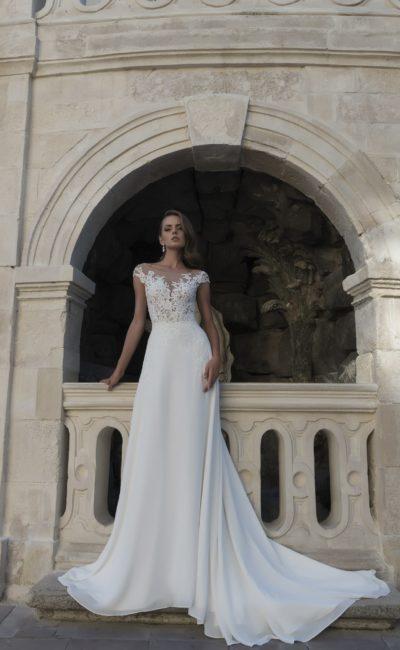 Свадебное платье с полупрозрачным верхом с кружевом и эффектной юбкой со шлейфом.