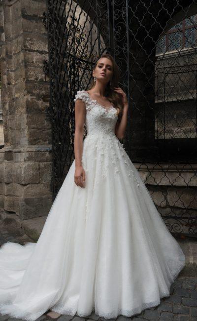 Свадебное платье «принцесса» с округлым вырезом декольте и нежной объемной отделкой.
