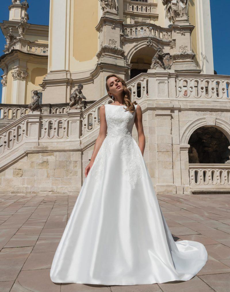 Атласное свадебное платье с вырезом «бато» и царственным длинным шлейфом на пышной юбке.