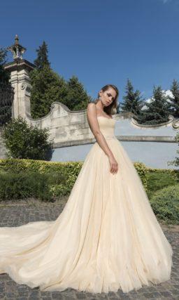 Пышное свадебное платье пастельного желтого оттенка с открытым декольте и сияющим поясом.