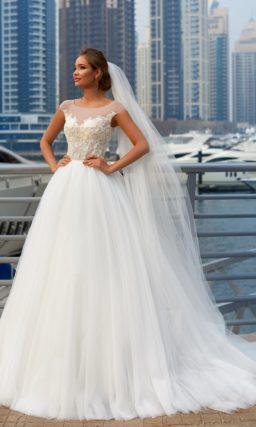 Пышное свадебное платье с закрытым лифом, покрытым вышивкой, и многослойным подолом.