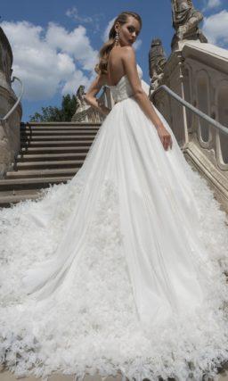 Кокетливое свадебное платье пышного кроя с открытым декольте и объемной отделкой юбки.