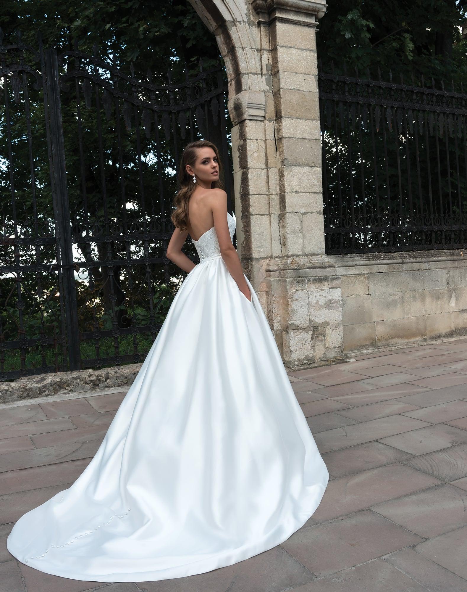 Пышное свадебное платье со скрытыми карманами и кружевным открытым корсетом.