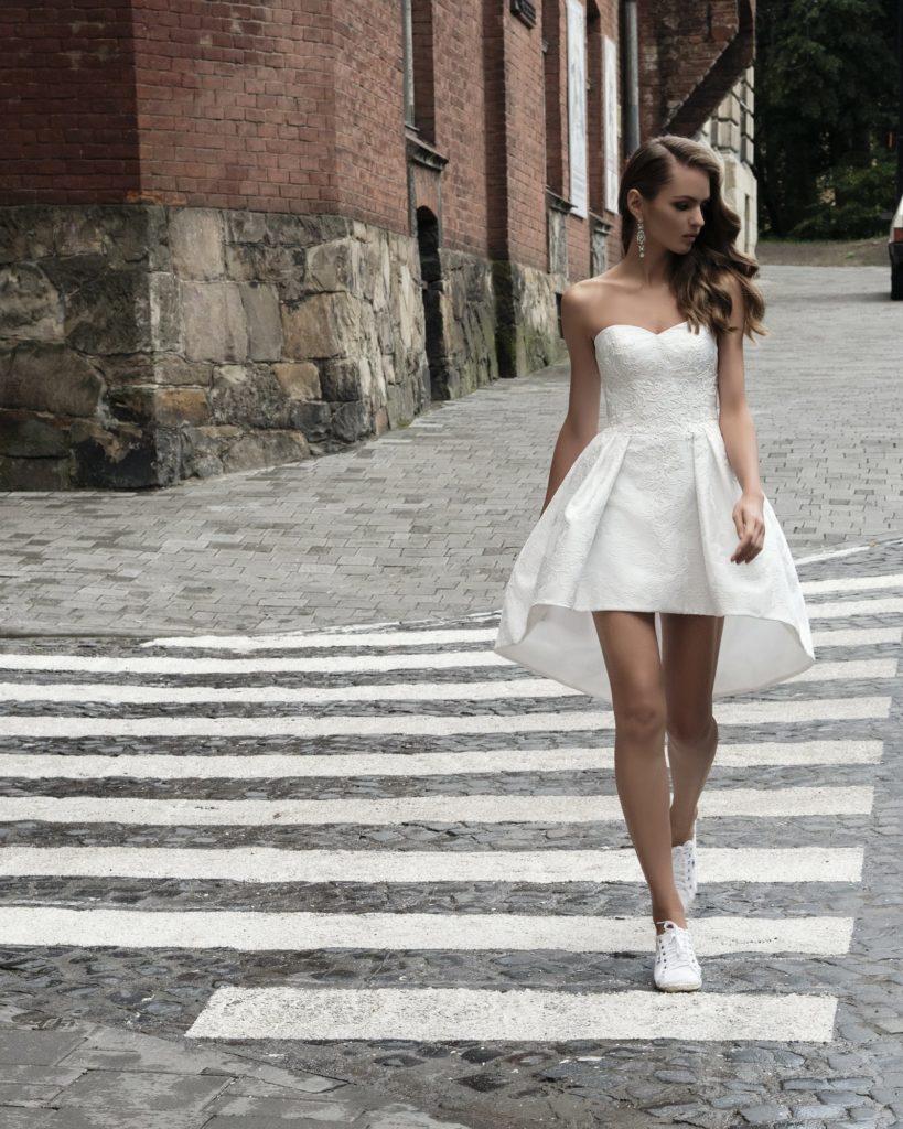 Кокетливое свадебное платье с юбкой длиной до середины бедра и открытым лифом.