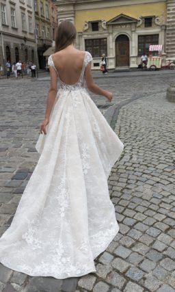 Свадебное платье цвета слоновой кости с пышной юбкой, укороченной спереди.