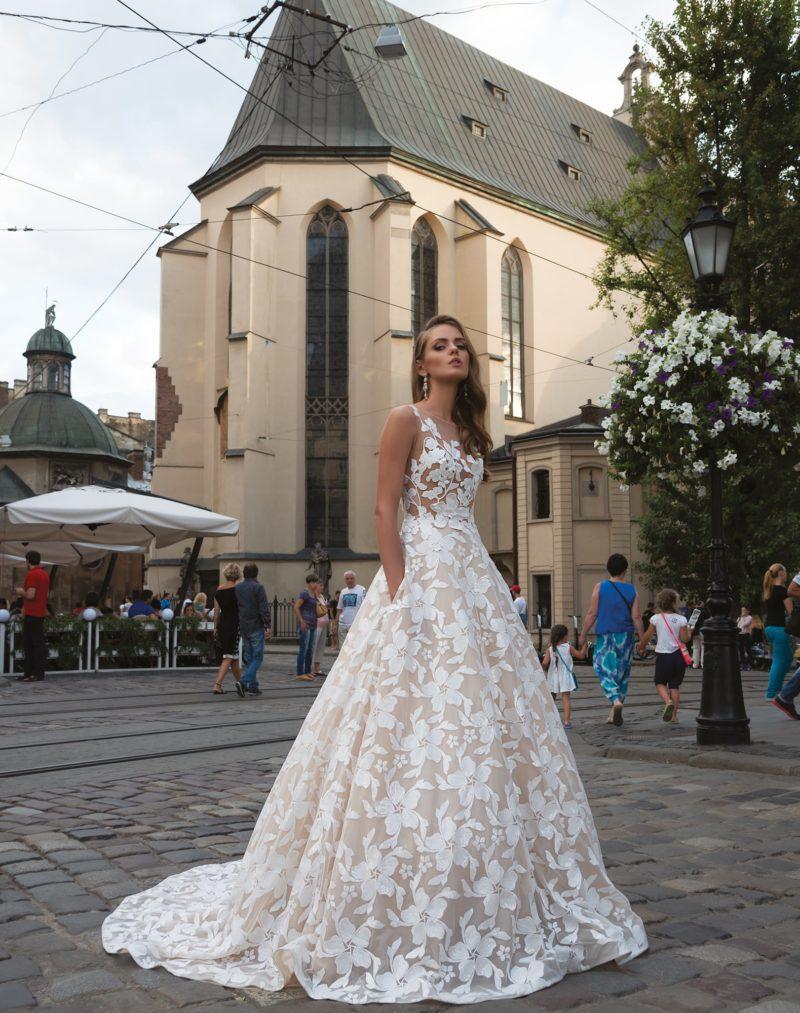 Свадебное платье пышного кроя с бежевой юбкой, покрытое крупным белоснежным декором.
