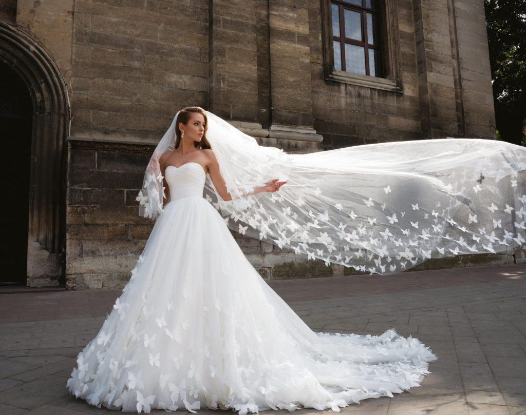 Очаровательное свадебное платье с открытым лифом и отделкой белыми бабочками по подолу.