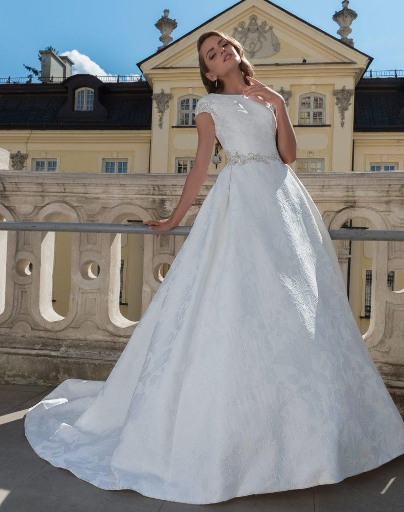 Свадебное платье из фактурной ткани, с вырезом «бато» и элегантным коротким рукавом.
