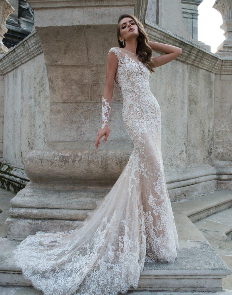 Бежевое свадебное платье облегающего кроя, полностью покрытое тонким белым кружевом.