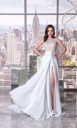 Прямое свадебное платье с разрезом сбоку подола и бежевым корсетом под кружевом.