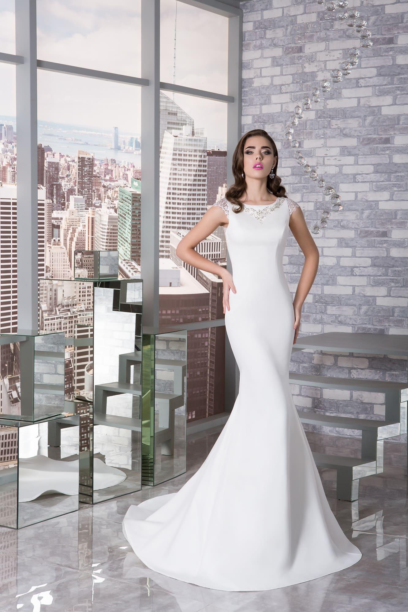 Облегающее свадебное платье с вырезом под горло и кружевными рукавами-крылышками.