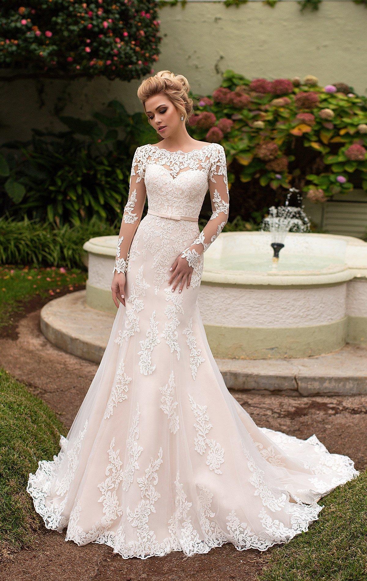 Кремовое свадебное платье «русалка» с длинным фактурным рукавом и вырезом под горло.