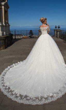 Пышное свадебное платье с узким поясом, портретным вырезом и длинным кружевным рукавом.