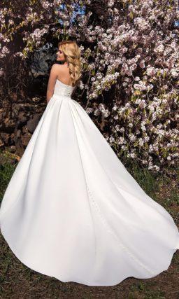 Кружевное свадебное платье с атласной верхней юбкой и узким поясом, украшенным бантом.