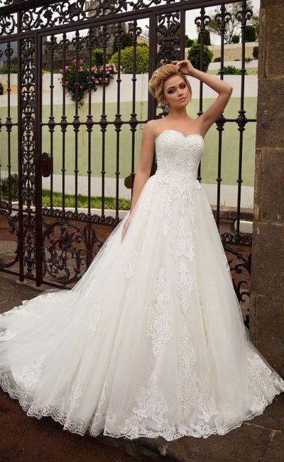Изысканное свадебное платье с открытым декольте и крупной кружевной отделкой по всей длине.