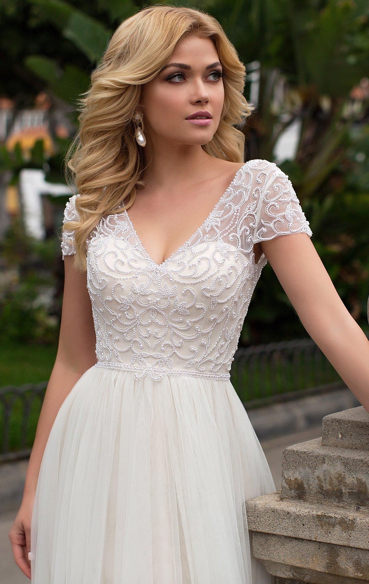 Прямое свадебное платье с короткими рукавами и небольшим V-образным вырезом.